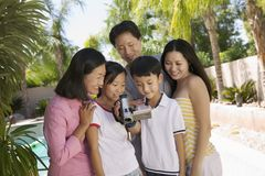 Famille par la piscine dans l'arrière-cour regardant la vue de face d'écran de caméra vidéo Photos libres de droits