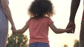 Famille parfaite tenant des mains, enfant adopté soutenu par les parents affectueux banque de vidéos