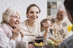 Famille parlant et appréciant le dîner image stock