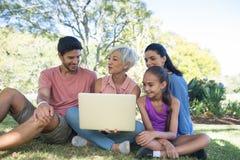 Famille parlant tout en à l'aide de l'ordinateur portable dans le parc Photos libres de droits