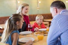 Famille parlant tout en appréciant l'apéritif dans le restaurant Photographie stock