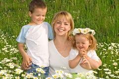 Famille parmi des fleurs photos stock