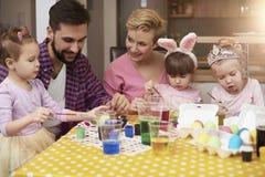 Famille peignant des oeufs de pâques Photos libres de droits