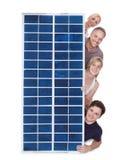 Famille piaulant par le panneau solaire Photos stock