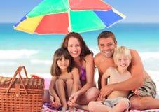Famille pique-niquant sous un parapluie de solénoïde Photographie stock libre de droits