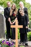 Famille pleurant à la tombe sur le cimetière image stock
