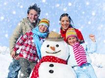 Famille posant avec un bonhomme de neige dehors Photo stock