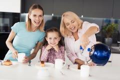 Famille posant dans la cuisine en cours de boire de thé Une femme agée verse le thé d'une théière dans une tasse Photographie stock