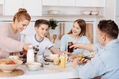 Famille positive agréable ayant le repas de matin ensemble Images stock