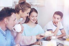 Famille positive appréciant le petit déjeuner ensemble Image stock