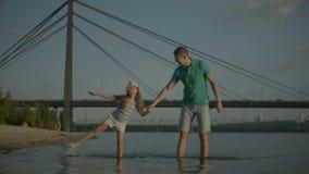 Famille positive faisant un tour le long de plage au coucher du soleil banque de vidéos