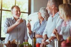 Famille positive se reposant ensemble dans la cuisine Photo stock