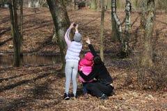 Famille pour une promenade Le papa montre la fille sur l'écureuil, qui se repose sur l'arbre La fille prend des photos de l'écure Images libres de droits