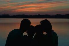 Famille près de la rivière contre le coucher du soleil Images stock