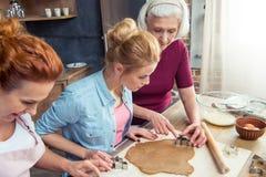 Famille préparant des biscuits de pain d'épice Photos libres de droits