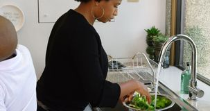 Famille préparant la nourriture dans la cuisine à la maison 4k banque de vidéos