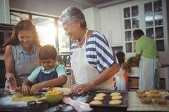 Famille préparant le dessert dans la cuisine images libres de droits