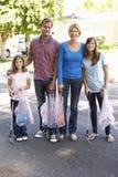 Famille prenant des ordures dans la rue suburbaine photos libres de droits