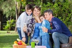 Famille prenant l'autoportrait par Smartphone à Photos stock