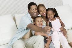 Famille prenant la photo de la famille sur le sofa avec le téléphone d'appareil-photo photo libre de droits