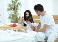 Famille prenant le petit déjeuner sur le lit dans la chambre à coucher Photo stock