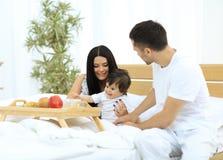 Famille prenant le petit déjeuner sur le lit dans la chambre à coucher Photos libres de droits