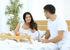 Famille prenant le petit déjeuner sur le lit dans la chambre à coucher Image libre de droits