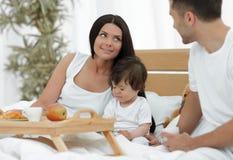 Famille prenant le petit déjeuner sur le lit dans la chambre à coucher Photos stock