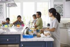 Famille prenant le petit déjeuner et faisant des déjeuners dans la cuisine Images stock
