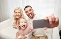 Famille prenant le selfie avec le smartphone à la maison Images libres de droits