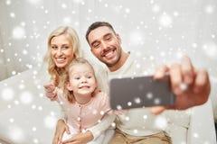 Famille prenant le selfie avec le smartphone à la maison Photographie stock libre de droits
