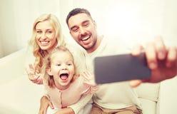 Famille prenant le selfie avec le smartphone à la maison Photo stock