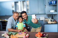Famille prenant le selfie tout en préparant la nourriture Image libre de droits