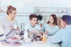 Famille quatre membered causant pendant le petit déjeuner Images libres de droits