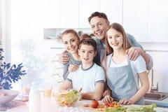 Famille rayonnante posant pour l'appareil-photo tout en faisant cuire Photos stock