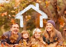 Famille recouverte avec la forme de maison se trouvant sur les feuilles sèches en parc photographie stock