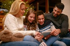 Famille regardant de vieilles photos de Noël Photographie stock libre de droits