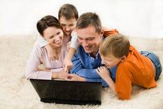 Famille regardant l'ordinateur portatif Image stock
