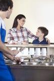 Famille regardant l'un l'autre tandis que serveur Preparing Ice Cream photo libre de droits