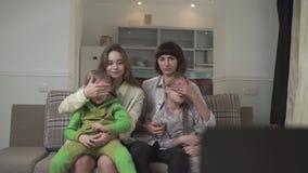 Famille regardant la TV se reposer sur le divan dans la chambre d'amis Des soeurs plus âgées ferment leurs yeux aux enfants en ra clips vidéos