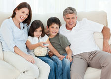 Famille regardant la TV tandis qu'elles mangent du maïs éclaté Photo libre de droits