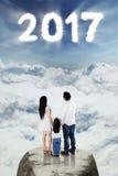 Famille regardant le numéro 2017 sur le ciel Image stock