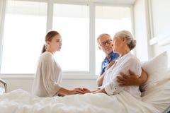 Famille rendant visite à la femme supérieure malade à l'hôpital Photographie stock libre de droits