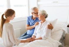 Famille rendant visite à la femme supérieure malade à l'hôpital Image stock