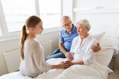 Famille rendant visite à la femme supérieure malade à l'hôpital Photo libre de droits