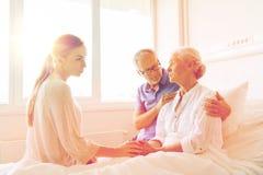 Famille rendant visite à la femme supérieure malade à l'hôpital Images libres de droits