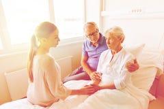 Famille rendant visite à la femme supérieure malade à l'hôpital Image libre de droits