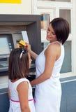 Famille retirant l'argent de par la carte de crédit à l'atmosphère Photographie stock