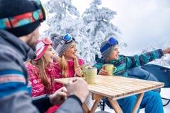 Famille riant et appréciant dans la boisson chaude à la station de sports d'hiver Photos libres de droits