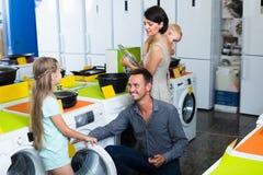 Famille riante choisissant la machine à laver Photo stock
